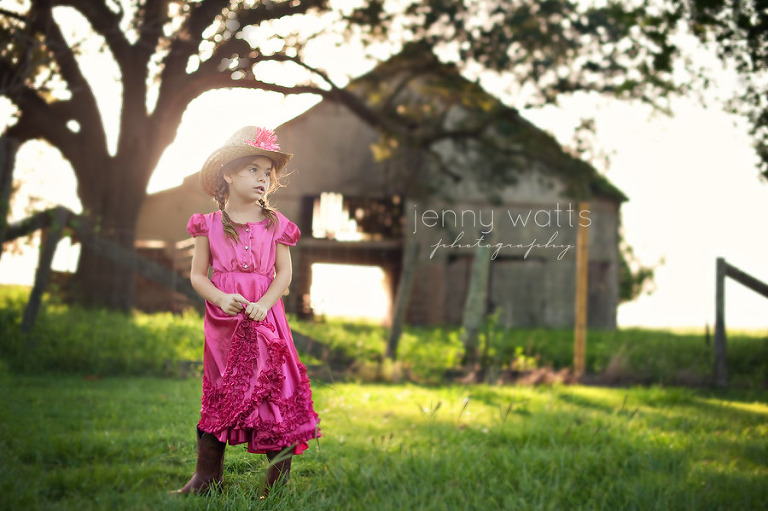 young girl in pink cowgirl outfit thinks outside barn on farm at sunset