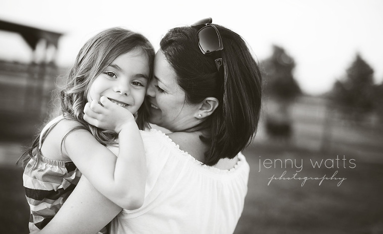 sweet moment of mother and daughter embracing and laughing at sunset