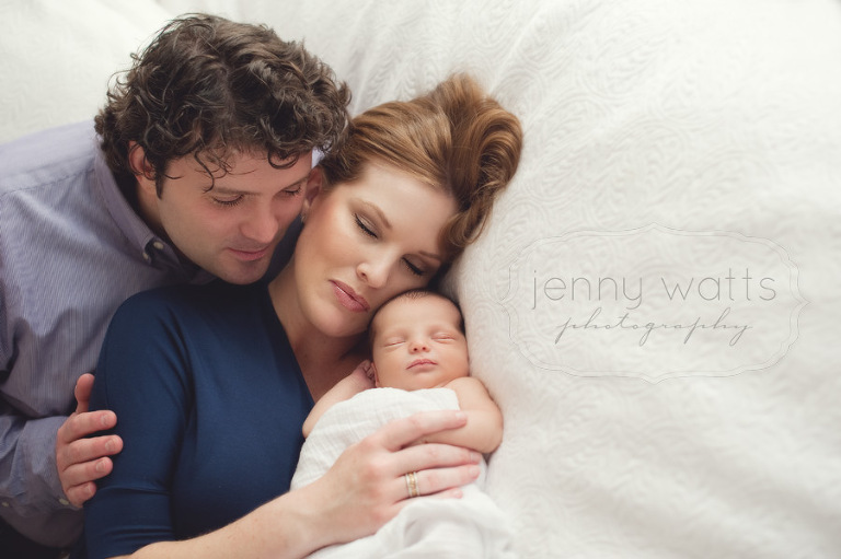 new parents snuggle with their newborn baby boy