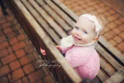 little girl sits on bench in park for her one year old photo