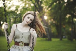 Young Teen girl sits on a swing at sunset before heading off to college